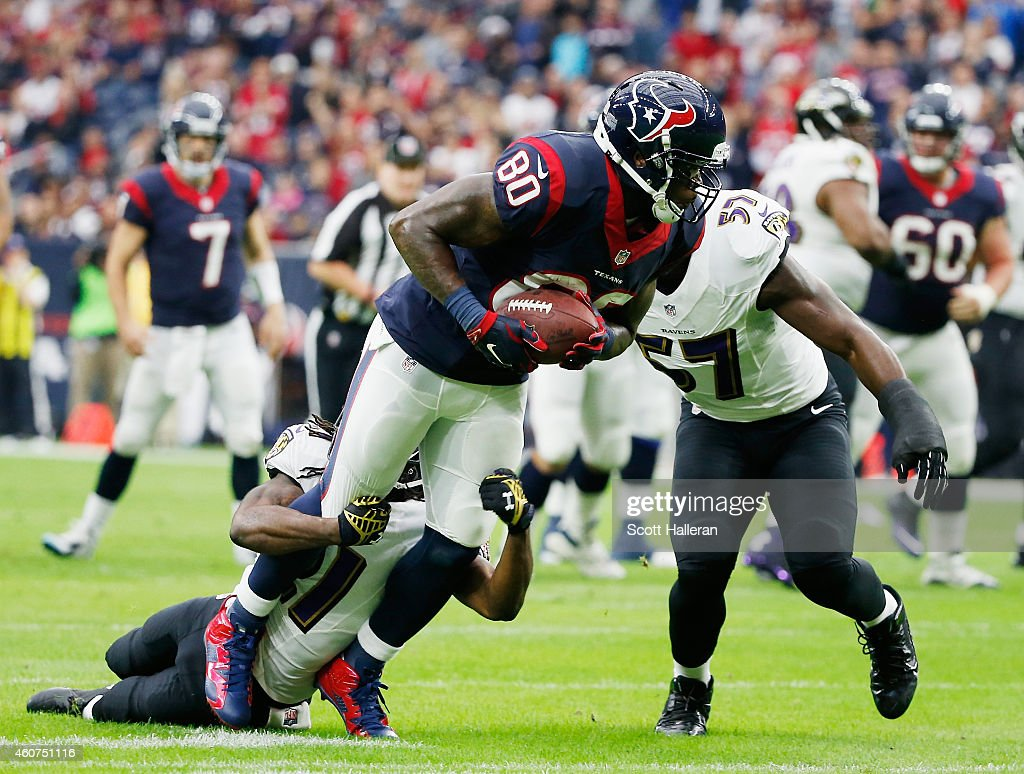 Andre Johnson #80 of the Houston Texans is tackled by Lardarius Webb #21 and C.J. Mosley #57 of the Baltimore Ravens during the game at NRG Stadium on December 21, 2014 in Houston, Texas.