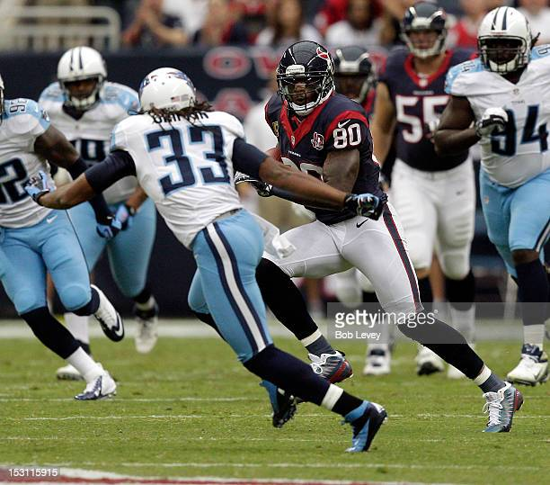 Andre Johnson of the Houston Texans runs with the ball after making a reception as Michael Griffin of the Tennessee Titans pursues at Reliant Arena...