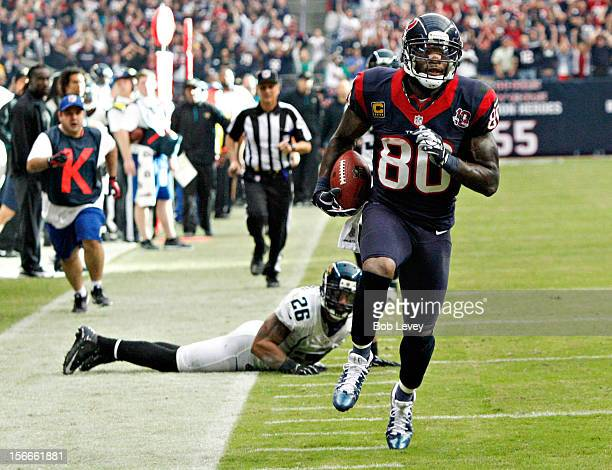 Andre Johnson of the Houston Texans scores on a 48 yard reception in overtime against the Jacksonville Jaguars as Dawan Landry of the Jacksonville...