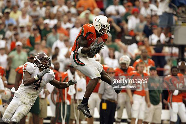 Andre Johnson of the University of Miami Hurricanes catches a 31 yard pass while being pressured by cornerback DeAngelo Hall of the Virginia...