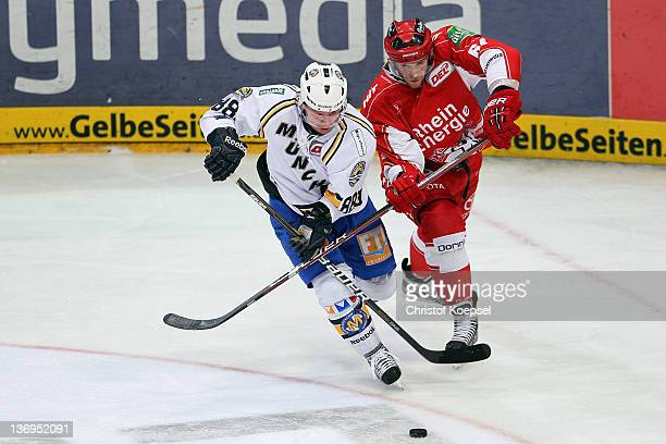 Andre Lakos of Koelner Haie uses his stick against Martin Schymainski of EHC Muenchen during the DEL match between Koelner Haie and EHC Muenchen at...