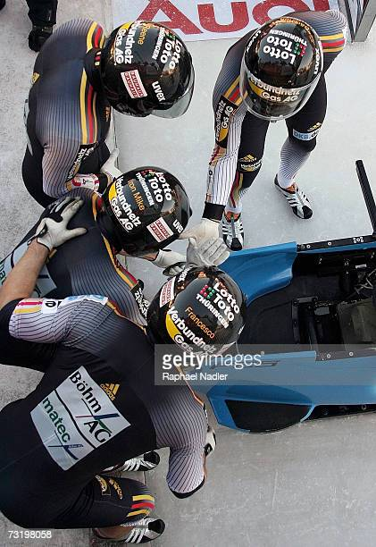 Andre Lange Rene Hoppe Kevin Kuske and Martin Putzeduring of Germany give a high five prior to the start of the Four Man Bobsleigh event at the...