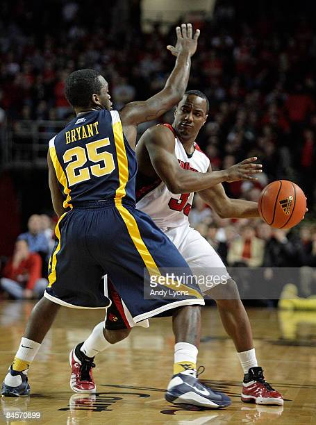 Andre McGee of the Louisville Cardinals looks to pass the ball while defended by Darryl Bryant of the West Virginia Mountaineers during the Big East...
