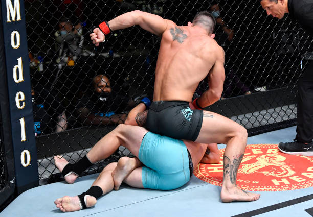 Andre Petroski punches Michael Gillmore in a middleweight fight during the UFC Fight Night event at UFC APEX on August 28, 2021 in Las Vegas, Nevada.