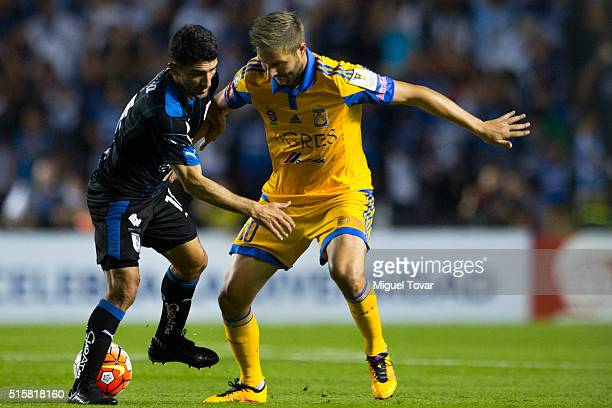 Andre Pierre Gignac of Tigres struggles for the ball with Antonio Naelson of Queretaro during the semifinal first leg match between Queretaro and...