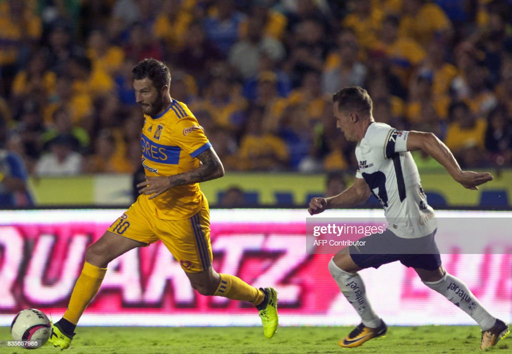 Andre Pierre Gignac (L) of Tigres vies for the ball with Abraham Gonzalez (R) of Pumas during their Mexican Apertura 2017 tournament football match at the Universitario stadium in Monterrey, Mexico on August 19, 2017. / AFP PHOTO / Julio Cesar AGUILAR