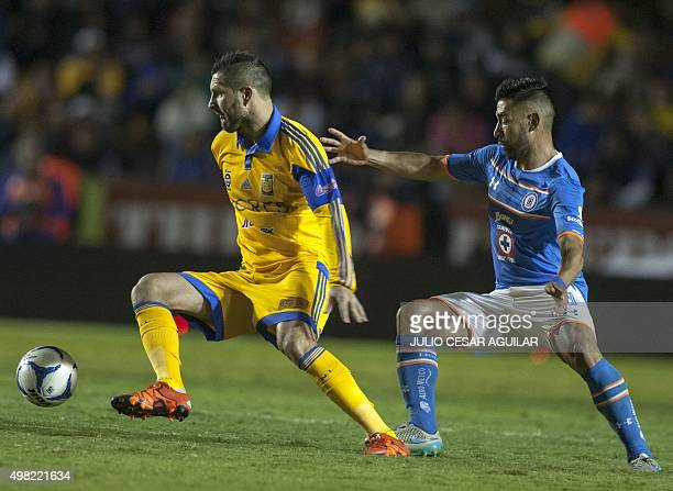 Andre Pierre Gignac of Tigres vies for the ball with Ariel Rojas of Cruz Azul during the Mexican Apertura 2015 tournament football match at the...