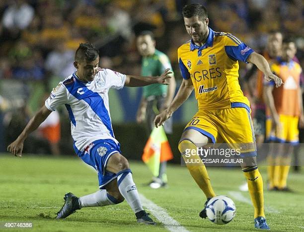 Andre Pierre Gignac of Tigres vies for the ball with Carlos Gutierrez of Puebla during the Mexican Apertura 2015 tournament football match at the...