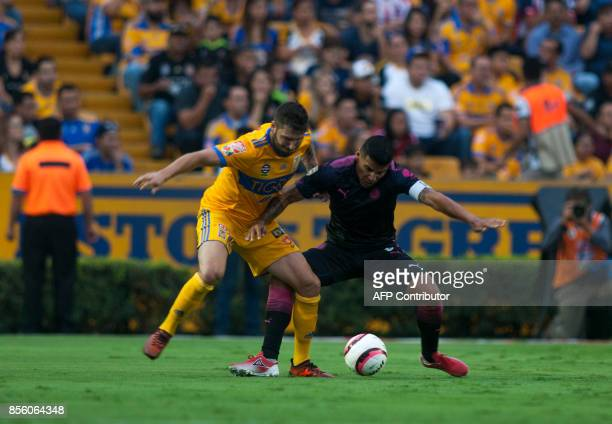 Andre Pierre Gignac of Tigres vies for the ball with Carlos Salcido of Chivas during their Mexican Apertura football tournament match at the...