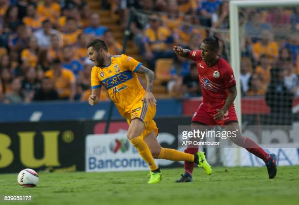 Andre Pierre Gignac of Tigres vies for the ball with Pedro Aquino of Lobos Buap during their Mexican Apertura 2017 tournament football match at the...