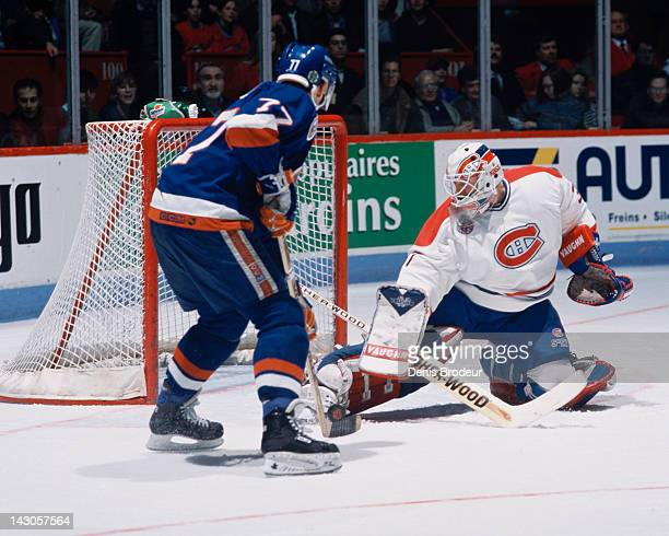 Andre Racicot of the Montreal Canadiens makes a save on Pierre Turgeon of the New York Islanders during a game Circa 1992 at the Montreal Forum in...