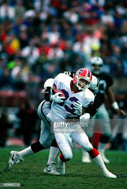 Andre Reed of the Buffalo Bills gets wrapped up by Ronnie Lott of Los Angeles Raiders during an NFL football game at the Los Angeles Memorial...