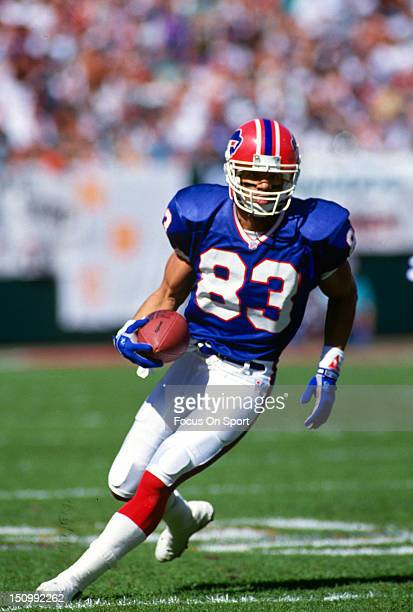 Andre Reed of the Buffalo Bills runs with the ball after a catch against the Miami Dolphins during an NFL football game at Joe Robbie Stadium October...