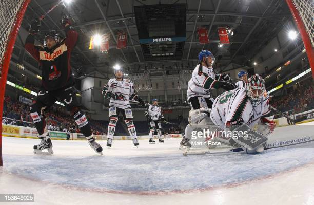 Andre Reiss of Hannover celebrates after he scores his team's 2nd goal over Patrick Ehelechner , goaltender of Augsburg during the DEL match between...