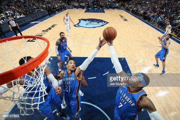 Andre Roberson and Carmelo Anthony of the Oklahoma City Thunder jump for the rebound against the Memphis Grizzlies on December 9 2017 at FedExForum...