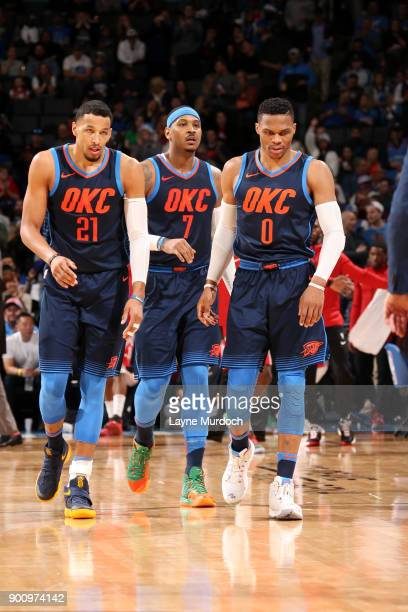 Andre Roberson Carmelo Anthony and Russell Westbrook of the Oklahoma City Thunder look on during the game against the Houston Rockets on December 25...