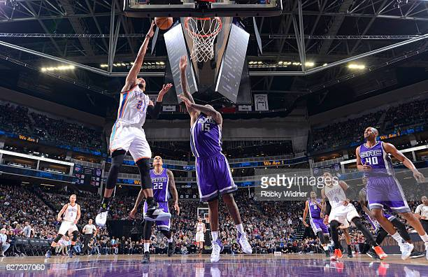 Andre Roberson of the Oklahoma City Thunder shoots a layup against DeMarcus Cousins of the Sacramento Kings on November 23 2016 at Golden 1 Center in...