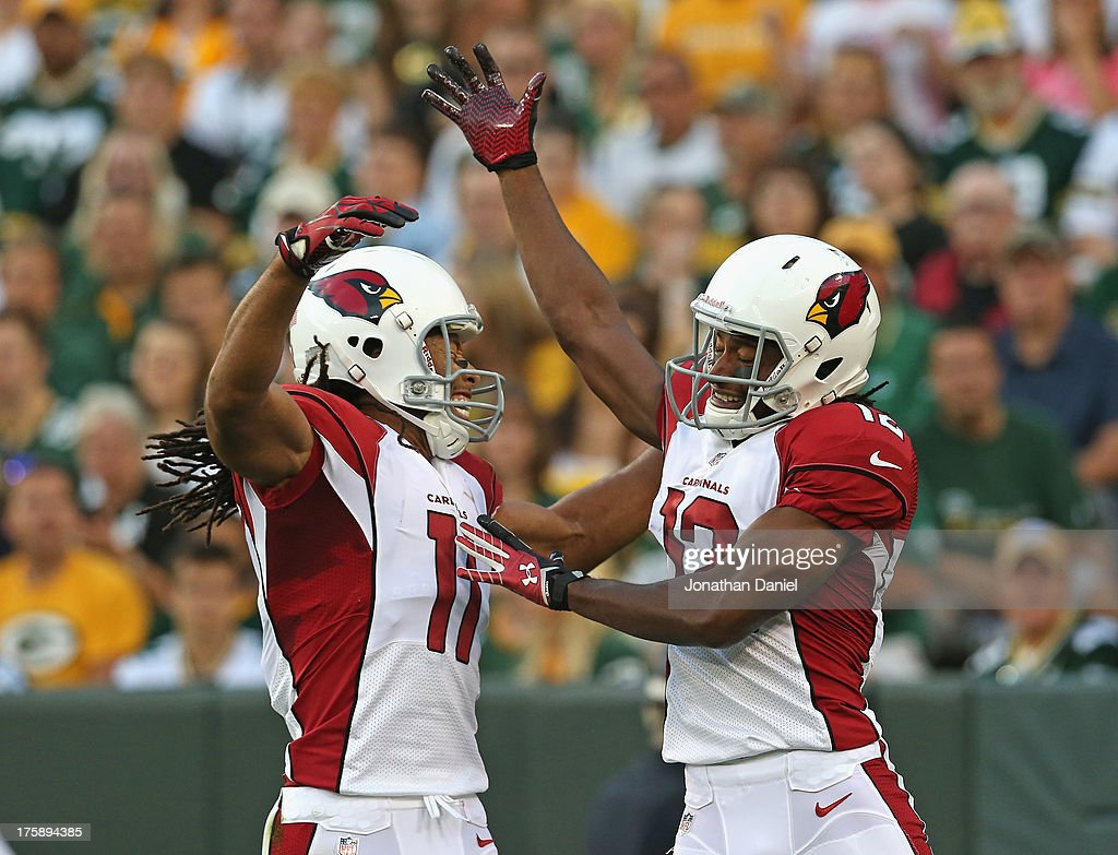 Andre Roberts #12 of the Arizona Cardinals (R) celebrates a touchdown catch with Larry Fitzgerald #11 against the Green Bay Packers at Lambeau Field on August 9, 2013 in Green Bay, Wisconsin.
