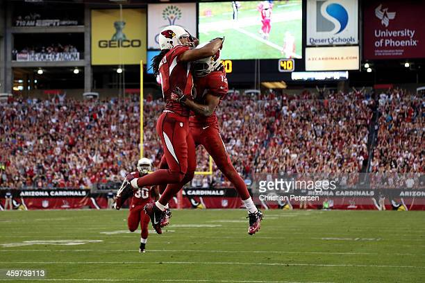 Andre Roberts of the Arizona Cardinals celebrates with teammate Larry Fitzgerald after scoring a 34 yard touchdown pass from Carson Palmer in the...