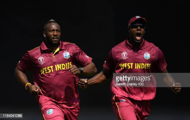 Andre Russell and Carlos Braithwaite of West Indies celebrates after taking the wicket of Usman Khawaja of Australia during the Group Stage match of...