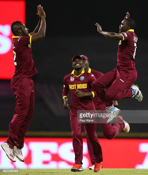 Andre Russell and Jerome Taylor of the West Indies celebrate the wicket of Rohit Sharma of India during the 2015 ICC Cricket World Cup match between...