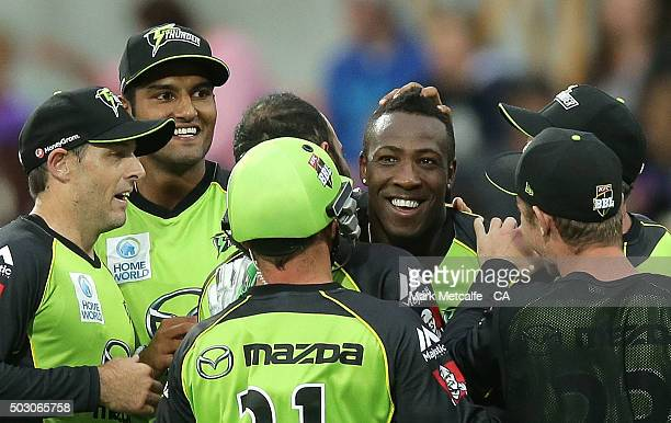 Andre Russell of the Thunder celebrates with team mates after taking a catch to dismiss Dan Christian of the Hurricanes of during the Big Bash League...