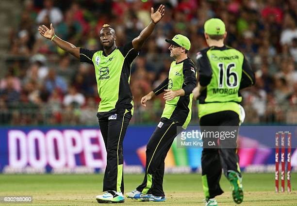 Andre Russell of the Thunder celebrates with team mates after taking the wicket of Jason Roy of the Sixers during the Big Bash League match between...