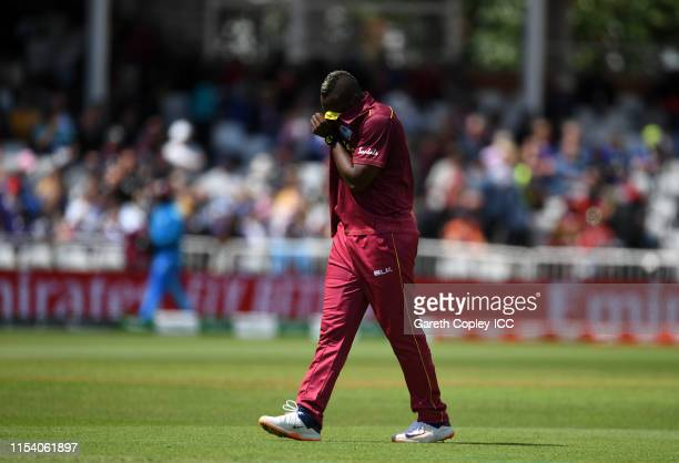Andre Russell of West Indies reacts after apeparing to pick up an injury before leaving the field during the Group Stage match of the ICC Cricket...
