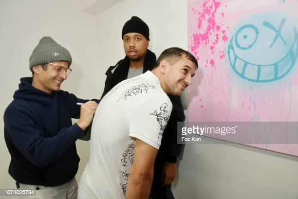 Andre Saraiva signs the T shirt of Franois Gautret during 'Andre x Futura Chez Nous' Painting Exhibition at Magda Danysz on December15 2018 in Paris...