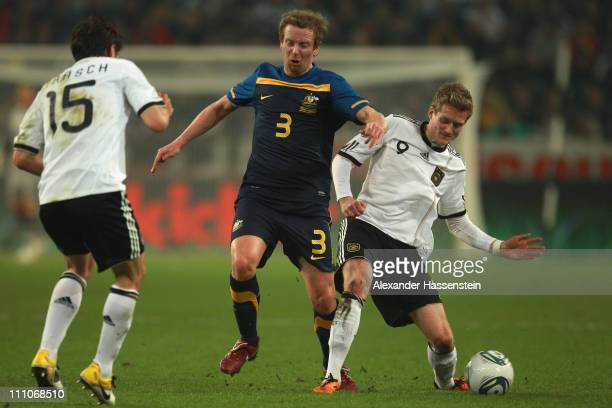 Andre Schuerle of Germany and his team mate Christian Traesch battle for the ball with David Carney of Australia during the international friendly...
