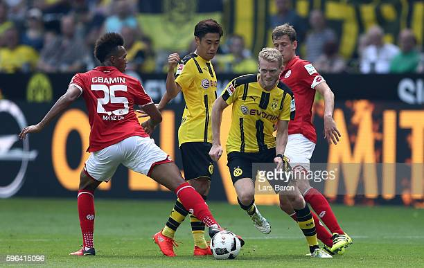 Andre Schuerrle of Dormtund is challenged by Jean Philippe Gbamin of Mainz during the Bundesliga match between Borussia Dortmund and 1 FSV Mainz 05...