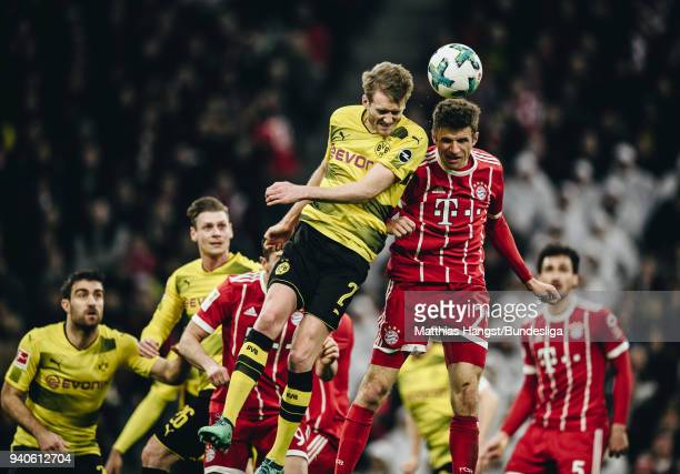 Andre Schuerrle of Dortmund jumps for a header with Thomas Mueller of FC Bayern Muenchen during the Bundesliga match between FC Bayern Muenchen and...