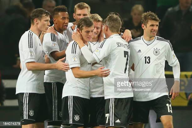 Andre Schuerrle of Germany celebrates scoring the second team goal with his team mates during the FIFA 2014 World Cup Qualifier Group C match between...