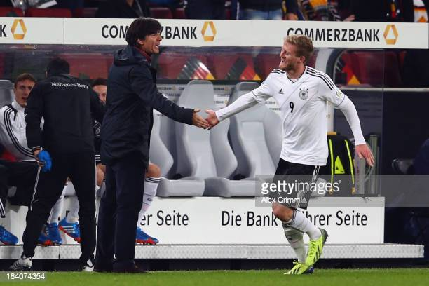 Andre Schuerrle of Germany celebrates with haed coach Joachim Loew after scoring his team's second goal during the FIFA 2014 World Cup Group C...