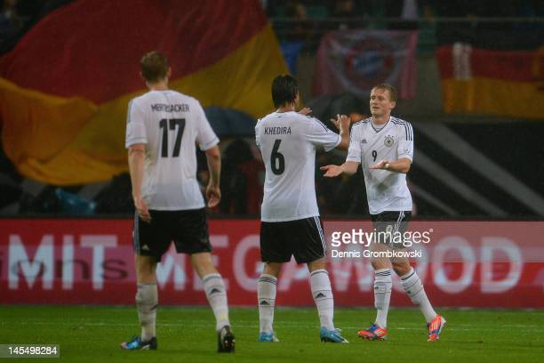 Andre Schuerrle of Germany celebrates with teammate Sami Khedira after scoring his team's second goal during the International friendly match between...