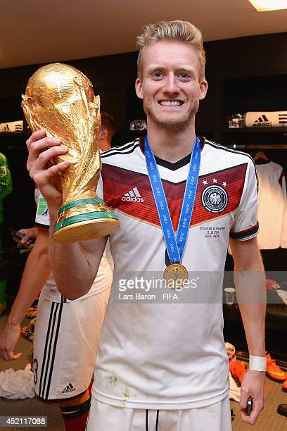 Andre Schuerrle of Germany holds up the World Cup trophy in the Germany dressing room after the 2014 FIFA World Cup Brazil Final match between...