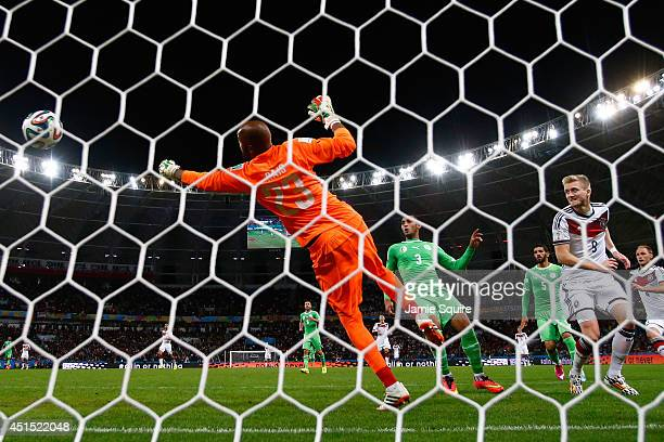 Andre Schuerrle of Germany scores his team's first goal past Rais M'Bolhi of Algeria in extra time during the 2014 FIFA World Cup Brazil Round of 16...