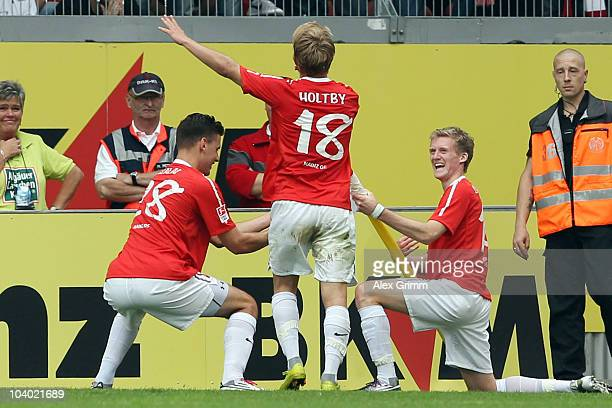 Andre Schuerrle of Mainz celebrates his team's second goal with team mates Lewis Holtby and Adam Szalai during the Bundesliga match between FSV Mainz...
