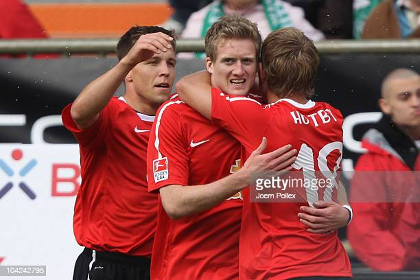 Andre Schuerrle of Mainz celebrates with his team mates Lewis Holtby and Radoslav Zabavnik after scoring his team's second goal during the Bundesliga...