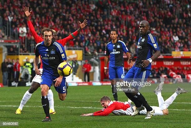 Andre Schuerrle of Mainz falls in the penalty area as Hamburg defenders follow the ball during the Bundesliga match between FSV Mainz 05 and...