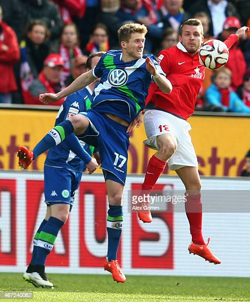 Andre Schuerrle of Wolfsburg jumps for a header with Daniel Brosinski of Mainz during the Bundesliga match between 1 FSV Mainz 05 and VfL Wolfsburg...
