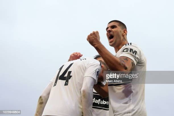 Andre Shurrle of Fulham celebrates with teammate Aleksandar Mitrovic after scoring his team's fourth goal during the Premier League match between...