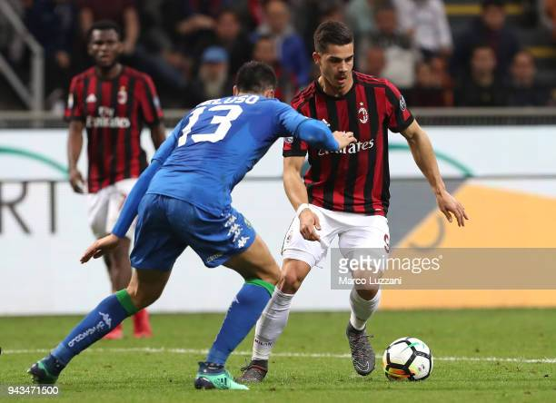 Andre Silva of AC Milan competes for the ball with Federico Peluso of US Sassuolo during the serie A match between AC Milan and US Sassuolo at Stadio...