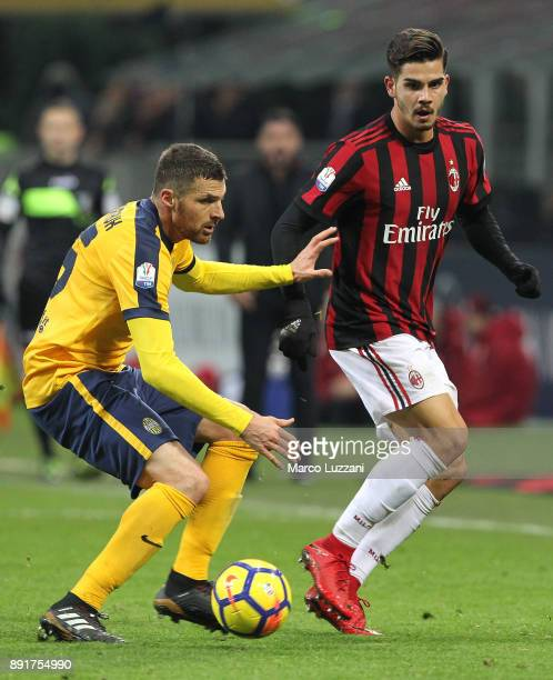 Andre Silva of AC Milan is challenged by Thomas Heurtaux of Hellas Verona FC during the Tim Cup match between AC Milan and Hellas Verona FC at Stadio...