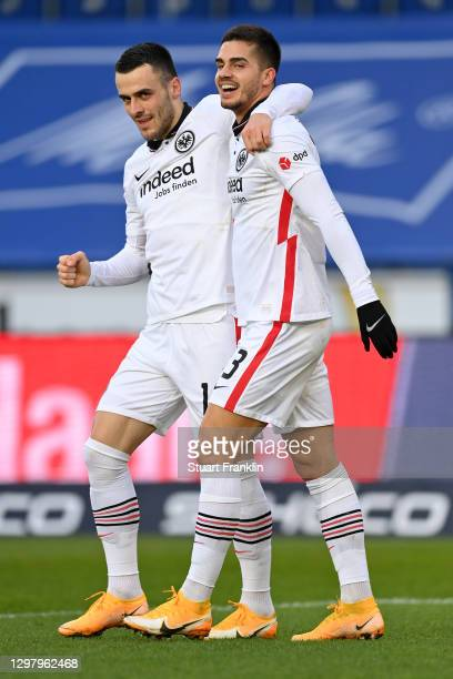 Andre Silva of Eintracht Frankfurt celebrates with teammate Filip Kostic after scoring their team's third goal during the Bundesliga match between...