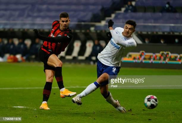 Andre Silva of Eintracht Frankfurt scores their team's first goal under pressure from Ozan Kabak of FC Schalke 04 during the Bundesliga match between...