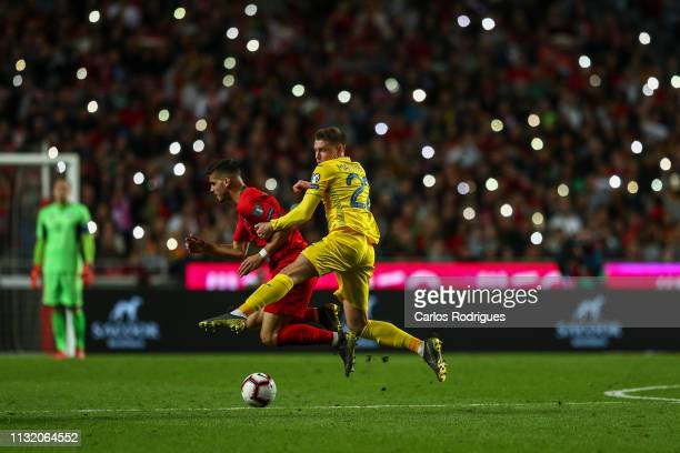 Andre Silva of Portugal and Sevilla FC tackled by Mykola Matviyenko of Ukraine during the 2020 UEFA European Championships qualifying match between...