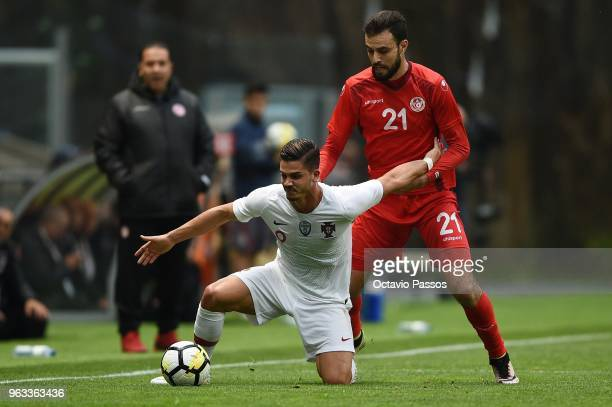 Andre Silva of Portugal competes for the ball with Hamdi Naguez of Tunisia during the international friendly football match against Portugal and...