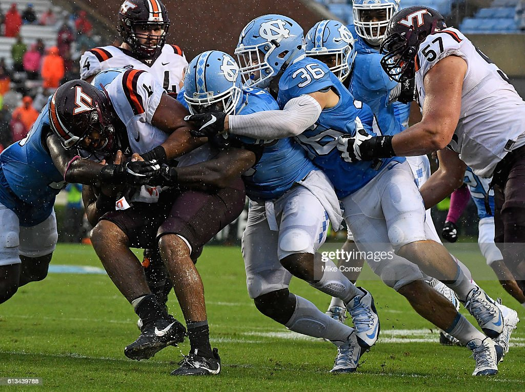 Andre Smith #56 of the UNC Tar Heels leads a tackle of Jerod Evans #4 of the Virginia Tech Hokies at Kenan Stadium on October 8, 2016 in Chapel Hill, North Carolina.