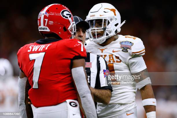 Andre Swift of the Georgia Bulldogs and PJ Locke III of the Texas Longhorns react after a play during the first half of the Allstate Sugar Bowl at...
